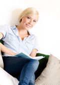 Female sitting on the sofa reads a book — Stock Photo