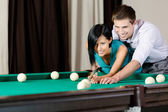 Man teaching girl to play billiards — Stock Photo