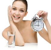Naked girl with glass of water shows alarm clock — Stock Photo