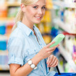 Half length portrait of girl at the store choosing cosmetics — Stock Photo