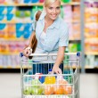 Girl with cart full of food in the shopping center — Stock Photo