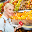 Girl at the shopping center choosing fruits hands apple — Stock Photo