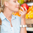 Girl at the shop choosing fruits smells apple — Stock Photo