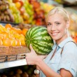 Girl at the store choosing fruits hands watermelon — Stock Photo