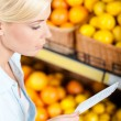 Stock Photo: Girl looks through shopping list near stack of fruits