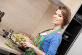 çekici bir kadın çizgili önlük sebze keser — Stok fotoğraf