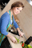 Beautiful woman in striped apron cuts vegetables — Stock Photo