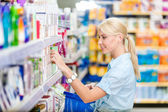 Profile of girl at the shop choosing cosmetics — Stock Photo