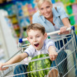 Little boy sits in the shopping trolley with watermelon — Stock Photo