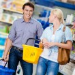 Couple in the shop with carts — Stockfoto