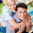 Girl embraces man in the shopping mall — Stock Photo