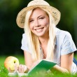 Girl in straw hat with apple reads book on the grass — Stock Photo