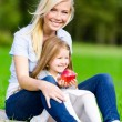 Mother and daughter with apple sitting on the green grass — Foto de Stock