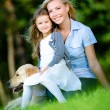 Mother and daughter with labrador sit on the grass — Stock Photo