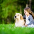 Little girl sitting on the grass with dog — Stock Photo