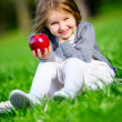Little girl with red apple sitting on the green grass — Stock Photo