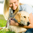 Portrait of girl with labrador on grass — Stock Photo