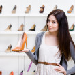 Half-length portrait of woman keeping shoe — Stock Photo