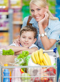 Mother and son with cart full of products in shopping center — Stock Photo