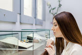 Close up view of girl looking at jewelry in glass case — Stock Photo