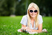 Female student reading book on the green grass — Stock Photo