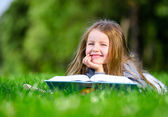 Little girl reads book on the grass — Stock Photo