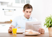 Reading man eats light breakfast in kitchen — Zdjęcie stockowe