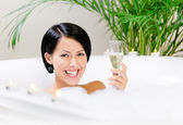 Lady taking a bath drinks champagne — Stock Photo