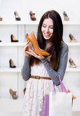 Half-length portrait of woman keeping heeled shoe — Stock Photo
