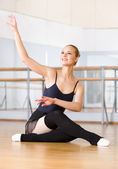 Ballet dancer does exercises sitting on the wooden floor — Stock Photo