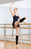 Ballet dancer dancing near barre in studio — ストック写真