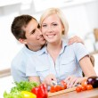 Male kisses pretty woman while she is cooking — Stock Photo