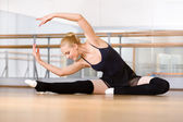 Bending ballerina stretches herself on the floor — Stock Photo