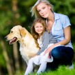 Mother and daughter with golden retriever are on the green grass — Stock Photo