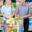 Couple in the shopping mall with cart full of food — Stock Photo