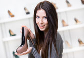 Woman keeping coffee-colored shoe — Stock Photo