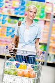 Fille avec panier plein de nourriture dans le magasin — Photo