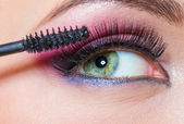 Close-up view of female eye and brush applying mascara — Stock Photo