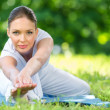 Woman stretching in park — Stock Photo