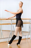 Ballet dancer dancing near barre — Stock Photo