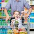 Little boy sitting in shopping trolley — Stock Photo