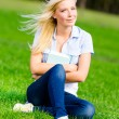 Student sits on the green grass — Stock Photo #33332607