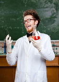Mad professor laughs handing conical flask — Stock Photo