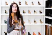 Woman can't choose stylish pumps — Stock Photo
