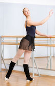 Ballerina dancing near barre in studio — Stock Photo