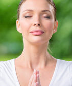 Woman with closed eyes prayer gesturing — Stock Photo
