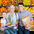 Family against shelves of fruits has shopping — Stock Photo #33809055
