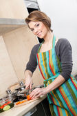 Woman in striped apron chops vegetables — Foto Stock