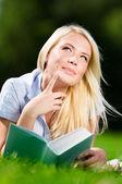 Sognare donna sdraiato sull'erba e leggendo il libro — Foto Stock