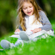 Sitting on the green grass girl reads book — Stock Photo #33812013